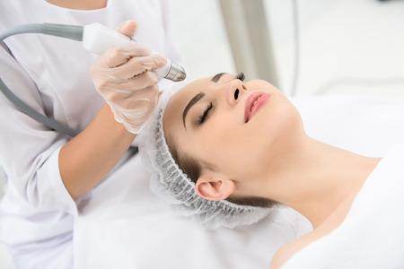 De jonge vrouw krijgt een behandeling van de laserhuid in gezonde schoonheidssalon. Ze ligt met ontspanning op de tafel. Haar ogen zijn gesloten