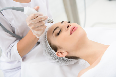 Young woman is getting a laser skin treatment in healthy beauty salon. She is lying on table with relaxation. Her eyes are closed Stock Photo