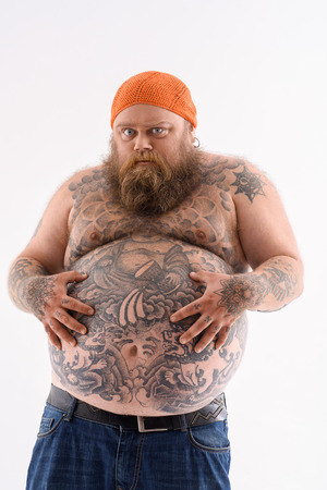 I am very hungry. Fat man is touching his naked belly with tattoo. He is standing and looking forward with desire. Isolated