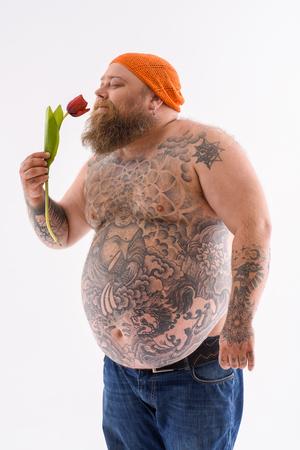 Gelukkige dikke man houdt tulp en ruikt het met plezier. Hij staat en lacht. Geïsoleerd