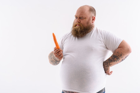 Fat man is holding carrot and looking at it pensively. Isolated and copy space in left side Stock Photo - 61356824