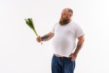 hesitation: I do not want to eat it. Fat bearded man is standing and holding leek. He is looking at vegetables with hesitation. Isolated