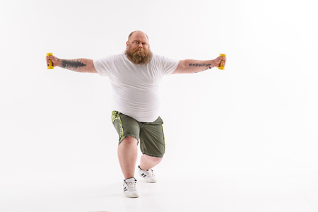 efforts: Fat man is lifting dumbbells with efforts. He is standing and stretching arms sideways. Isolated Stock Photo