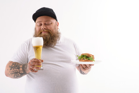 fatso: Happy male fatso is enjoying unhealthy beer and hamburger. He is standing and smiling. Isolated and copy space in eight side