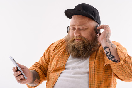 Thick man is enjoying music from headphones. He is holding mobile phone and relaxing. His eyes are closed with pleasure. Isolated Stock Photo