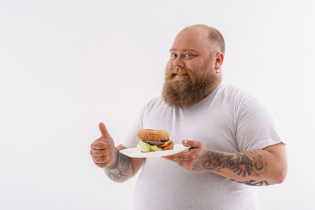 Happy thick man is holding plate with sandwich. He is giving thumb up and smiling. Isolated and copy space in left side Stock Photo