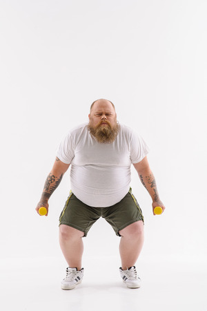 Strained fat man is trying to lift weights. He is standing and posing with efforts. Isolated Stock Photo