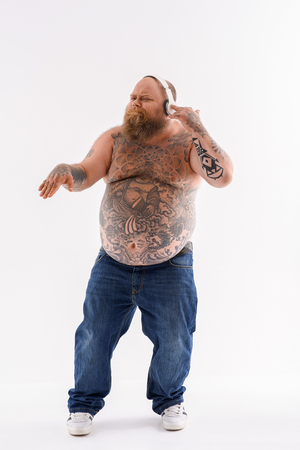 Cool fat man is listening to music with pleasure. He is touching headphones and dancing. Isolated Imagens