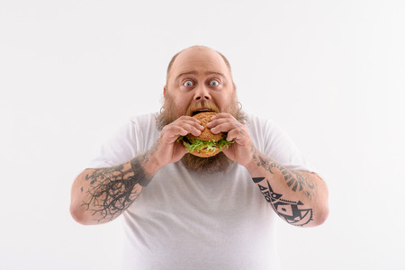Fat man is eating sandwich with enjoyment. He is standing and looking at camera with shock. Isolated