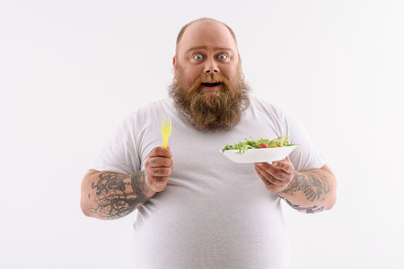 Joyful fat man is eating salad and smiling. He is standing and looking at camera with amazement. Isolated