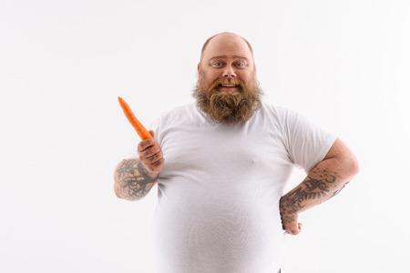 El hombre gordo alegre está sosteniendo la zanahoria y está sonriendo. Él está de pie y mirando a la cámara felizmente. Aislado Foto de archivo