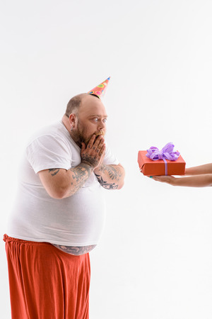 Thick man is celebrating his birthday. He is looking at gift box with shock. Man is standing with cone on head. Isolated Stock Photo