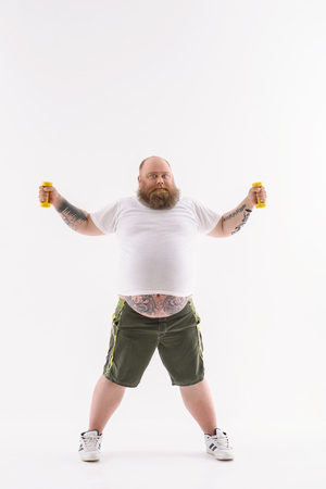 estereotipo: Fat man is training with weights. He is standing and posing. Man is looking at camera with motivation. Isolated