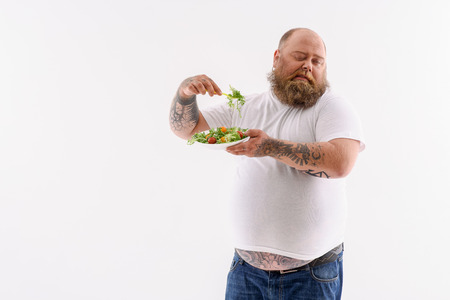 Fat man is forcing himself to eat salad. He is standing and holding plate. Fatty is expressing eversion. Isolated and copy space in left side