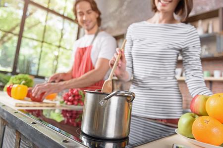 Het blije echtpaar kookt thuis samen. De vrouw mengt maaltijd in pot en het glimlachen. De mens bevindt zich en snijdt groenten