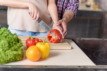 gentleness: Close up of young woman cutting vegetable in kitchen. Man is touching female hand with gentleness Stock Photo