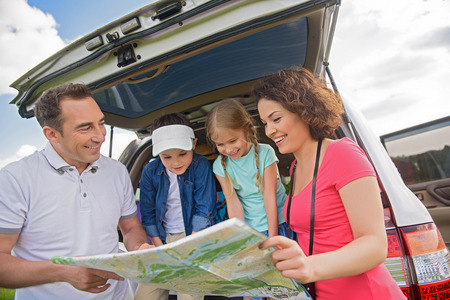 family planning: So many places to go. Close up of happy family planning their trip and looking at map, standing near car outside Stock Photo