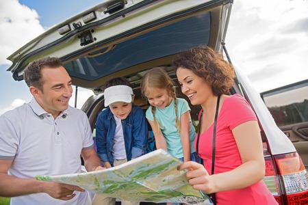 planificacion familiar: Tantos lugares a donde ir. Cierre de la familia feliz planificar su viaje y mirando el mapa, coloca cerca del coche fuera