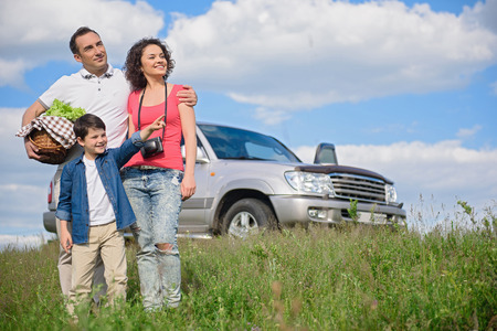 somewhere: Dad, what is it. Little boy showing his hand somewhere, standing next to parents with big car in background Stock Photo