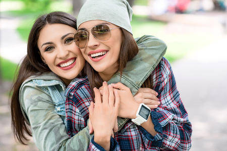 Carefree two sisters are hugging with love. They are looking at camera and smiling. Women are standing and relaxing in nature Stock Photo