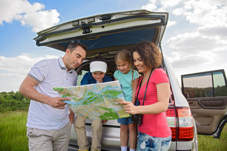 cropped shot: So many places to see. Cropped shot of young smiling family opening map and planning hiking adventure Stock Photo