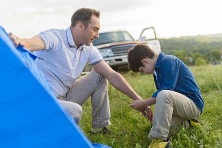 pitching: Outdoor adventures with dad. Close up photo of cute little boy helping his father pitching tent outdoors with car in background Stock Photo