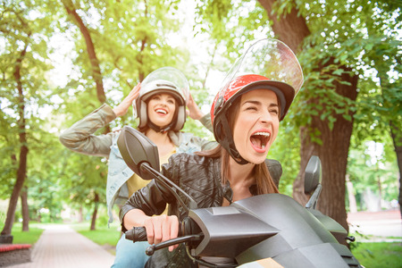 Happy female friends are driving a bike in park. Women are sitting and laughing