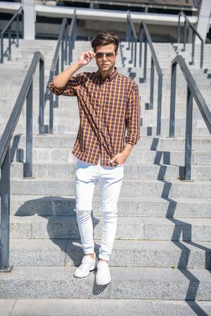 down stairs: Hombre joven con estilo está bajando escaleras al aire libre. Él está en contacto con las gafas de sol y mirando a la cámara con confianza