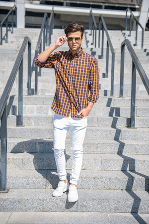 Stylish young man is going down stairs outdoors. He is touching sunglasses and looking at camera with confidence