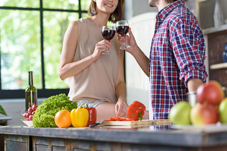 clinking: Cheers. Joyful married couple is clinking wineglasses and smiling. They are standing in kitchen and preparing dinner Stock Photo