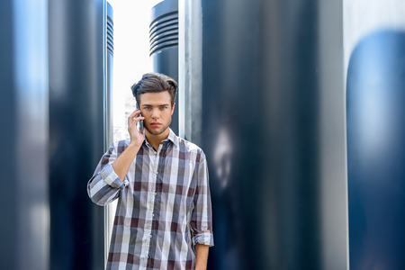 seriousness: Young man is talking on mobile phone. He is standing and looking at camera with seriousness