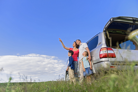 unsurpassed: Unsurpassed landscapes around us. Happy family standing near his car in field while mother pointing to sky