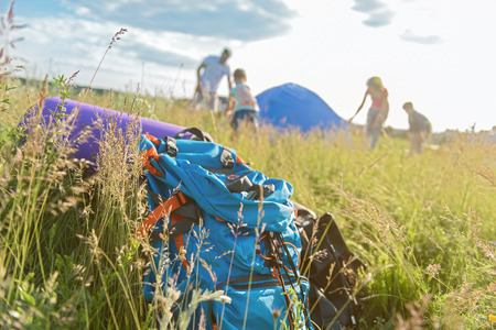 pitching: Family camping is family bonding. Close up of backpack lying on grass with family putting up tent together in background