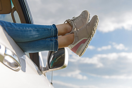 close out: Time to relax. Close up of woman legs out window in car above clouds Stock Photo