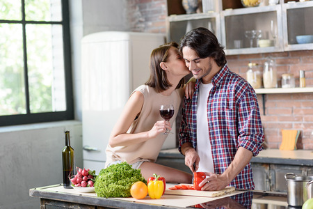 he she: Young man is preparing romantic dinner for his wife. He is cutting vegetable and smiling. Woman is kissing him with love. She is sitting on table in kitchen and holding wineglass