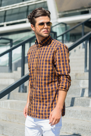 bajando escaleras: Pensive young man is standing on steps outdoors. He is looking aside seriously. Man is wearing sunglasses