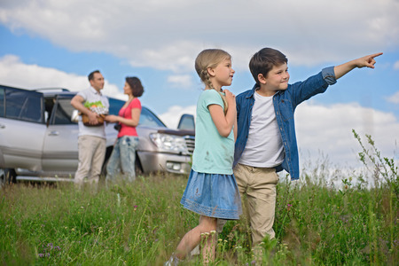 buddies: Travel buddies. Little brother showing something to his sister with parents talking near car in background