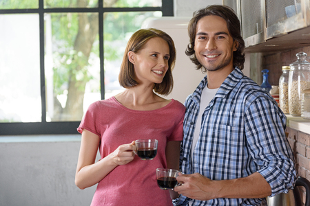 Happy loving couple is drinking coffee in kitchen. They are talking and smiling Stock Photo
