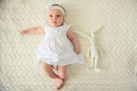 非常に幸せな赤ちゃんであります。白いドレスとヘッドバンド カメラにポーズと敷物の上に横たわる少女かわいい赤ちゃんのショットを閉じる