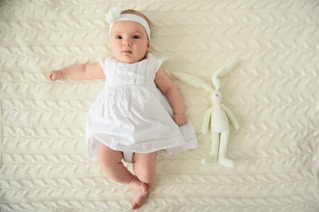 Be very happy baby. Close up shot of little cute baby girl in white dress and headband posing on camera and lying on rug Stok Fotoğraf - 61868352