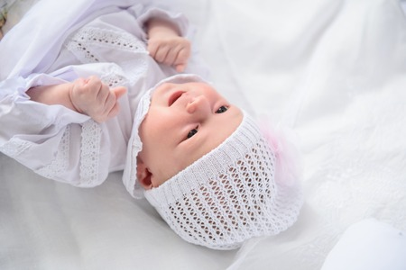 girl lying down: Looking at you. Portrait of adorable baby girl lying down on blanket and wearing in knitted cap isolated on white