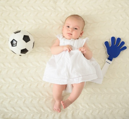 Smallest football fan. Top view of cute baby girl in beautiful white dress lying on rug beside football attributes