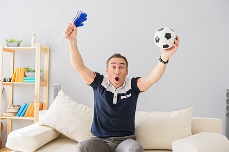 enthusiastically: I am the most ardent fan. Shot of handsome adult man celebrating while watching sports match on tv at home, holding football attributes Stock Photo