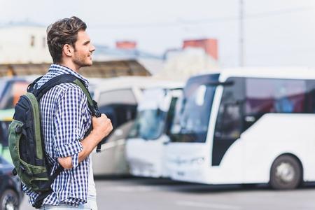 Traumhafter männlicher Tourist ist bereit zu reisen. Er sieht den Bus mit Inspiration an. Der Mensch steht und lächelt