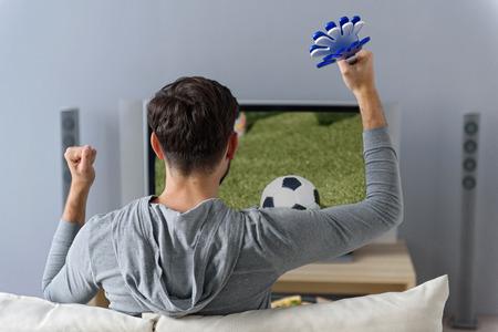 talisman: Alegre aficionado al fútbol está animando a su equipo. Él está sentado en el sofá y mirando la pantalla con concentración. El hombre está haciendo gestos de esperanza