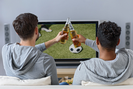they are watching: Two young men are watching football with concentration. They are sitting on sofa and clinking bottles of beer. Focus on their back Stock Photo