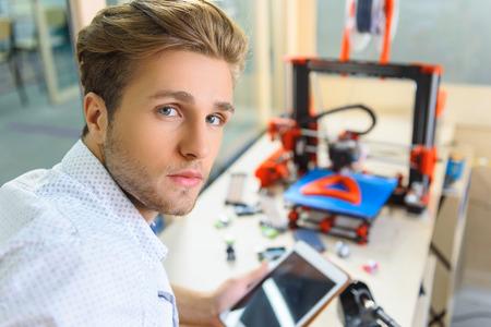 Inteligentny młody człowiek korzysta z drukowania 3d w biurze. Trzyma tabletkę i patrzy na kamerę z ufnością Zdjęcie Seryjne