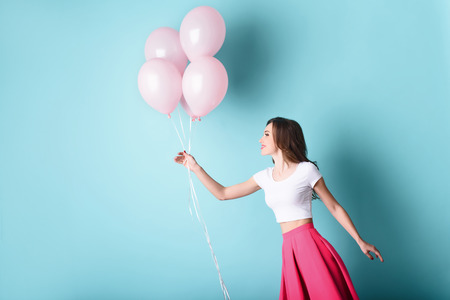 Carefree woman playing with pink balloons. Isolated and copy space on left side