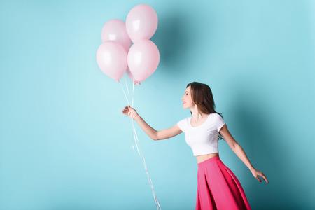 Muchacha libre está jugando con globos de color rosa. Ella está posando y sonriendo. espacio aislado y la copia en el lado izquierdo Foto de archivo - 62639451