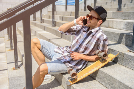 Cheerful male skater is talking on mobile phone and laughing. He is sitting on stairs outdoors and relaxing